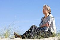 Senior woman relaxing on a beach (thumbnail)