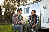 Two teenage boys sat outside a caravan