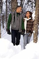 A mature couple walking through snow