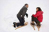 A couple crouching in the snow wearing snowshoes