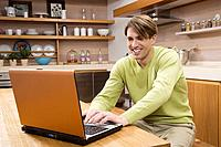 Young man sitting in kitchen using laptop, portrait