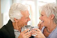 Senior couple toasting each other, smiling, portrait