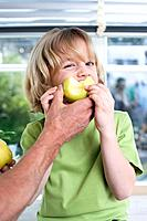 Boy 8_9 biting apple, portrait