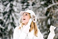 Austria, Salzburger Land, Altenmarkt, Young woman frolicking in the snowy woods