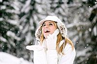 Austria, Salzburger Land, Altenmarkt, Young woman using phone in the snowy woods