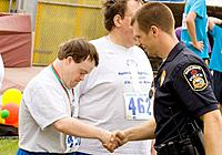Proud athlete shakes hands with policeman at award ceremony, Special Olympics, U of M Bierman Field complex, Minneapolis, Minnesota, USA