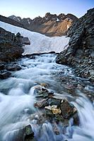 Water rushes from below a melting snow bridge at the outlet to Wrights Lake below Mt  Sneffels, San Juan Mountains, Colorado, USA