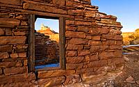 Temple Mountain is framed through the window of an old stone house left behind by a miner in the Temple Mountain Ghost Town, San Rafael Swell, Utah, U...