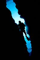 Micronesia, Yap, Diver silhouetted through reef canyon.