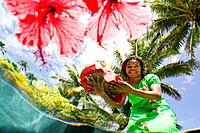 Underwater view looking up at young Fijian woman serving colorful tropical drinks  Hibiscus flowers floating in pool