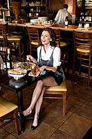 Woman eating in restaurant and laughing