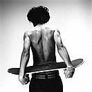Rear view of shirtless man with skateboard