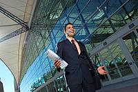 Businessman walking outside office building and smiling low angle view