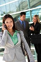 Businesswoman using mobile phone with colleagues in background outdoors