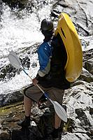 Man carrying kayak looking at river back view
