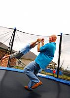 Side profile of a mid adult man playing with his son on a trampoline