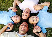 High angle view of a mid adult couple lying on grass in a circle with their two sons