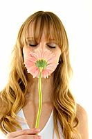 Close_up of a young woman smelling a flower