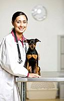 Hispanic female veterinarian and dog