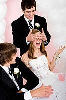 Hispanic man covering girlfriend's eyes at prom