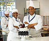 Multi_ethnic pastry chefs next to cake
