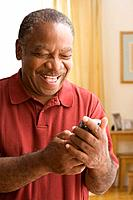 Senior African man looking at cell phone