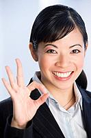 Asian businesswoman making okay hand gesture