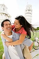 Asian man giving girlfriend piggyback ride