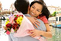 Asian couple hugging with flowers (thumbnail)