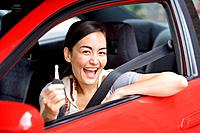 Asian woman holding car key in car