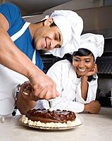 Hispanic male pastry chef decorating cake