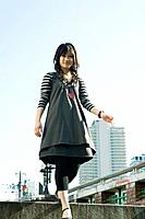 Young woman walking in urban setting, smiling at camera, low angle view