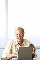 Man making on-line purchase with credit card, smiling at camera