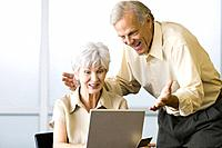 Excited mature couple looking at laptop computer together, woman holding credit card