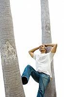 Man leaning against palm tree, eyes closed, listening to headphones