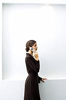 Well-dressed young female using cell phone, standing, side view
