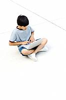 Boy sitting cross-legged on the ground, using laptop