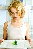 Woman holding plate with a single piece of broccoli , looking down