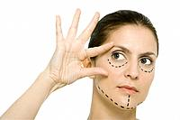 Woman with plastic surgery markings on face, touching face, looking away