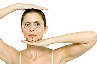 Woman with plastic surgery markings on face, framing head with hands, looking at camera