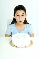 Girl blowing out candle on birthday cake, portrait