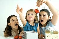 Girls opening presents, one holding ornament, other reaching up, mother watching