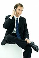 Businessman using cell phone, smiling at camera