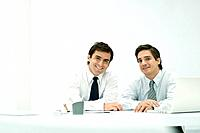 Male business partners sitting side by side at desk, smiling at camera