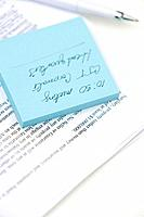 Message written on adhesive note and document, close-up