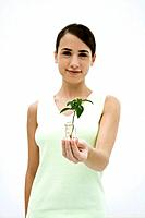 Woman holding seedling in vase, smiling at camera