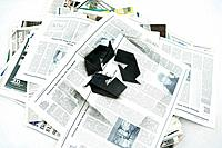 Pile of newspapers spray painted with recycling symbol