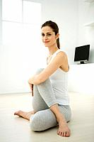 Woman doing spinal twist, smiling at camera