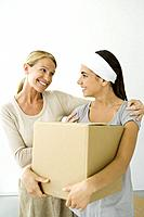Mother with arm around daughter´s shoulder, daughter holding cardboard box, both smiling