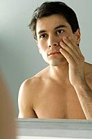 Bare-chested man looking at self in mirror, touching face